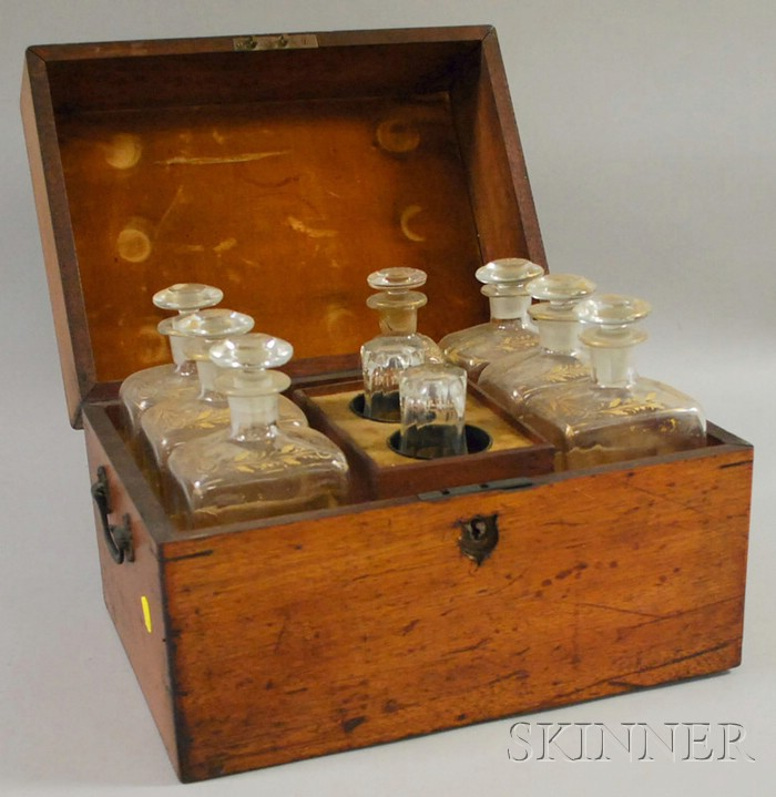 Walnut Spirit Chest with a Partial Set of Seven Gilt-decorated Colorless Blown   Glass Decanters and a Pair of Glasses
