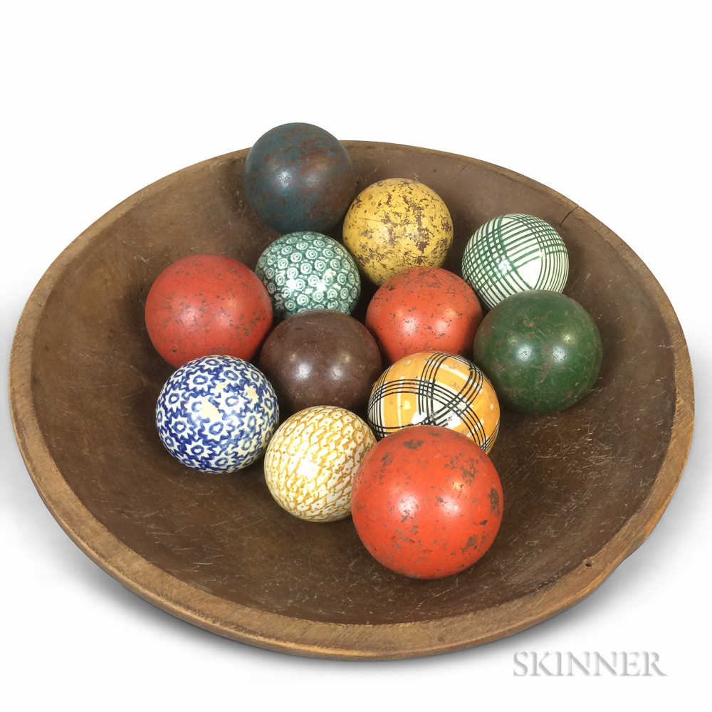 Red-painted and Turned Pine Bowl and Twelve Wood and Ceramic Carpet Balls