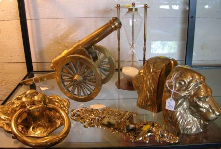 Brass and Wood Cannon Model, a Pair of Brass Lion Bookends, a Lion Doorknocker, an Hour Glass, and a Matchstrike.