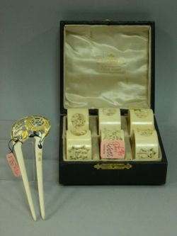 Cased Set of Six Carved Ivory Napkin Rings and a Gilt and Mother-of-Pearl Decorated Ivory Hair Comb.