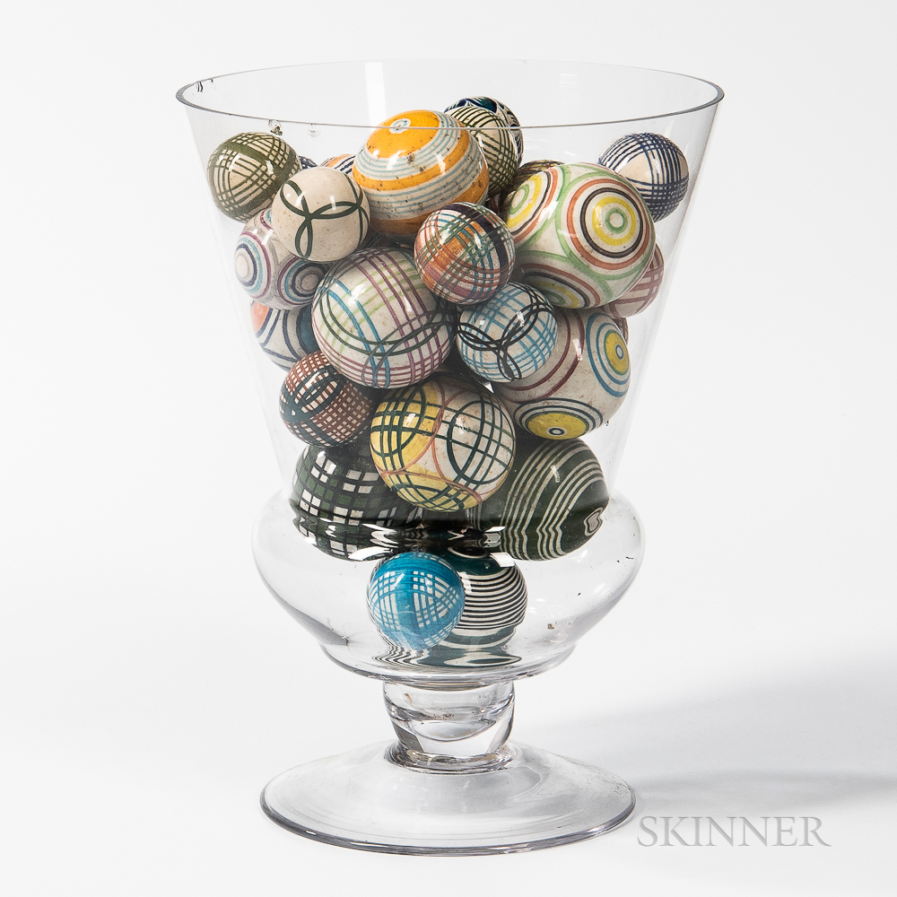 Approximately Thirty Carpet Balls in a Large Blown Glass Vase
