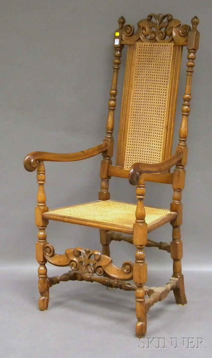 Colonial Revival Carved Walnut Armchair with Caned Back and Seat.