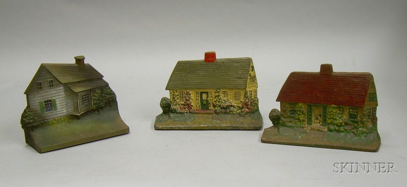 Two Painted Cast Iron Cottage Doorstops and a Bradley & Hubbard Painted Cast Iron House Doorstop.