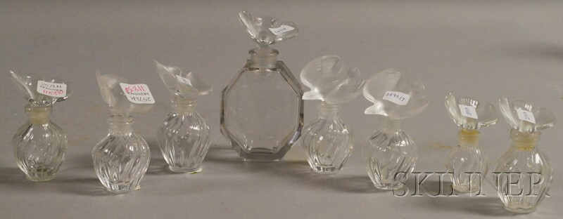 Seven Lalique Nina Ricci Perfume Glass Bottles and a Baccarat Nina Ricci Perfume Glass Bottle.