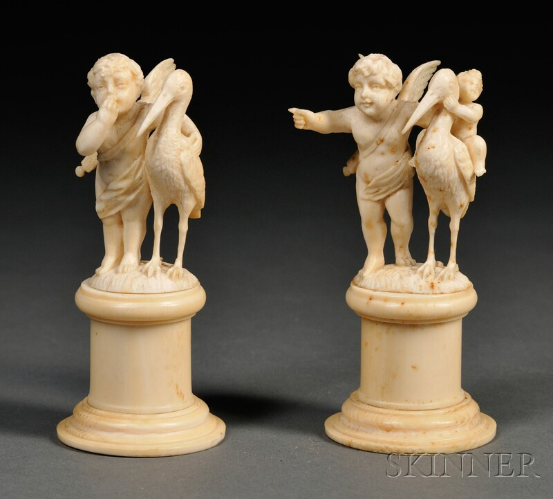 Two European Carved Ivory Figures of Cherubs with Storks