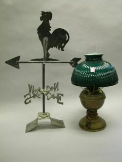 Black Painted Sheet Iron Rooster Weather Vane and a Kerosene Lamp with Green Cased Glass Shade.