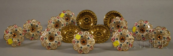 Set of Four Pressed Brass Curtain Tiebacks and a Set of Ten Gilt Porcelain Curtain Tiebacks.