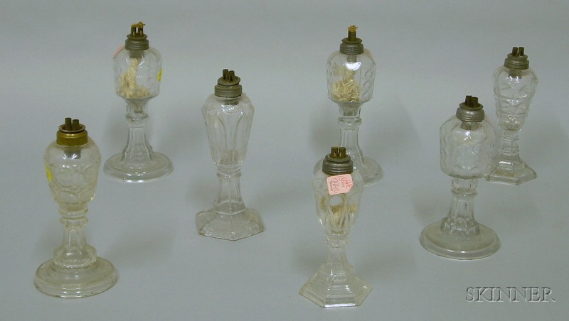 Seven Colorless Pressed Pattern Glass Lamps