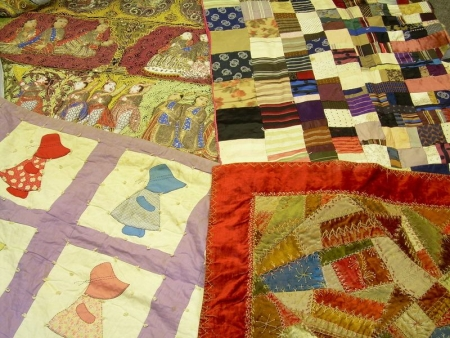 Asian Textile Panel, an Embroidered Crazy Quilt, a Pieced Silk Quilt, and a Pieced Cotton Quilt.