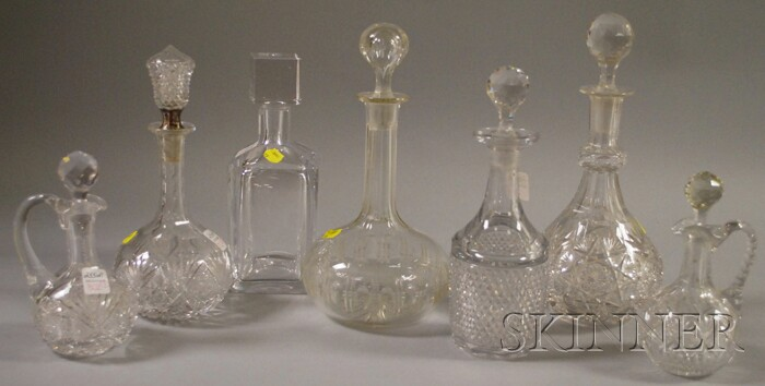 Four Colorless Cut Glass Decanters, Two Cruets, and a Kosta Boda Crystal Decanter.