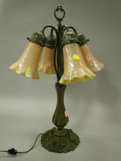 Patinated Cast Iron Table Lamp with Four Iridescent Art Glass Sconce Shades.