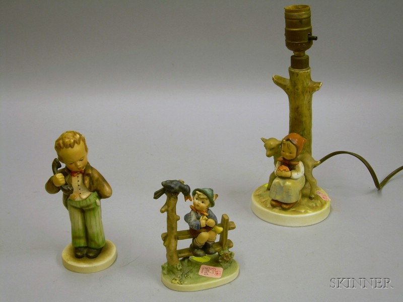 Two Hummel Ceramic Figures and a Hummel Ceramic Figural Table Lamp Base.