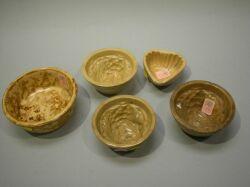 Four Small Yellowware Pudding Molds and a Rockingham Glaze Bowl.