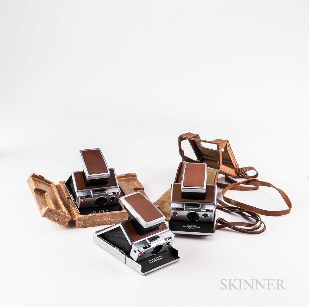 Three Polaroid SX-70 Cameras in Silver and Brown Leather