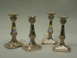 Set of Four Classical Revival Silver Plated Candlesticks. rectangular removable sconce, with reeded nozzle, tapered stem ending in reed