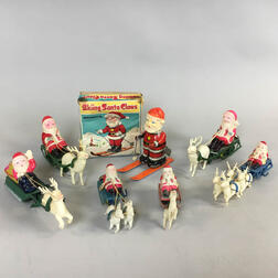 Seven Celluloid and Tin Wind-up Santa Claus and Sleigh Toys