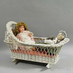 Two Dolls and a White Wicker Cradle